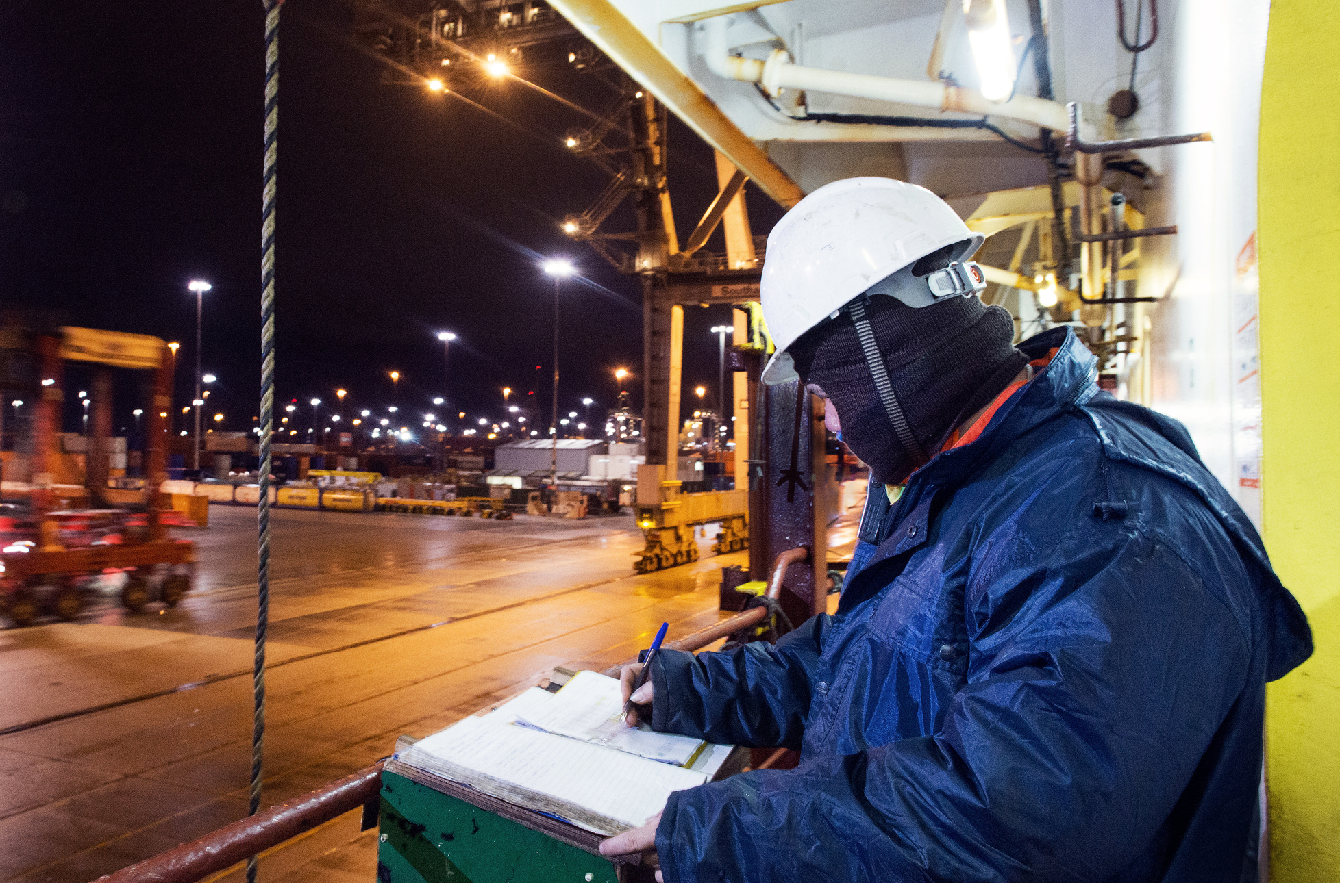 Seafaring workman completing paperwork on site at night